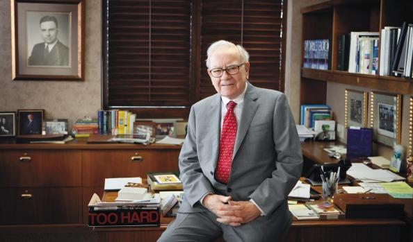 Buffett in een pose voor zijn schrijfdesk.