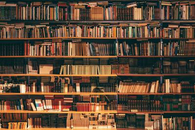 Foto van een bibliotheek die vol staat met boeken over beleggen.